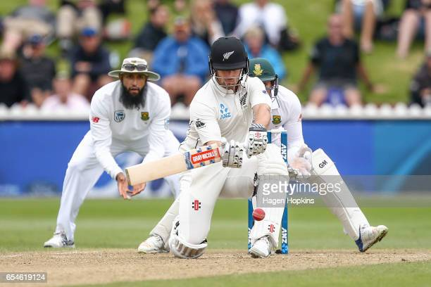 Neil Broom of New Zealand bats while Quentin de Kock and Hashim Amla of South Africa look on during day three of the test match between New Zealand...