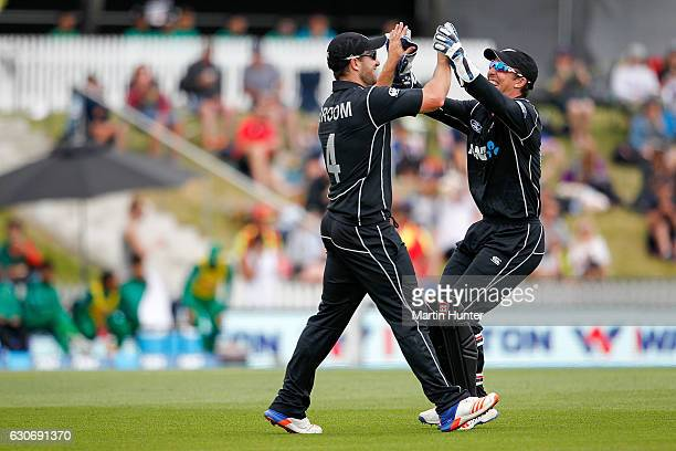 Neil Broom of New Zealand celebrates with team mate Luke Ronchi after taking a catch during the third One Day International match between New Zealand...
