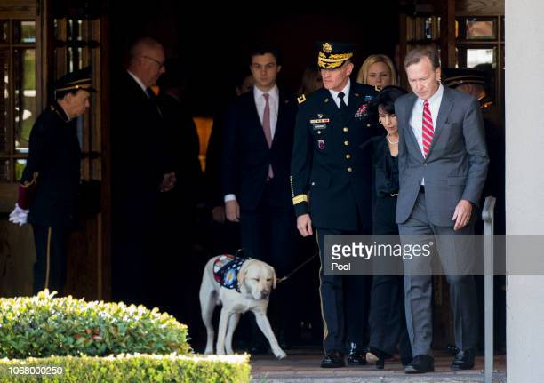 Neil Bush and his wife Maria with a service dog exit the funeral home before the flagdraped casket of the remains of President George HW Bush are...