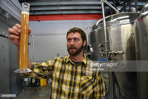 Neil Fischer owner and head brewer at WeldWorks Brewing pulls a sample of Juicy Bits a very popular hazy IPA beer at the brewery June 29 2016