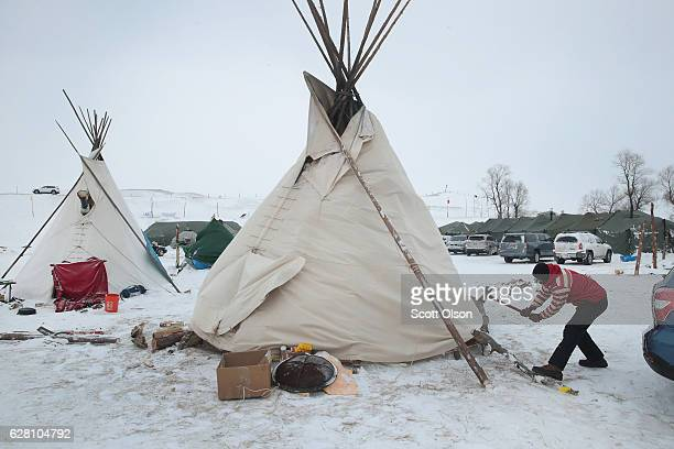 Neil Gordon secures the base of a teepee at Oceti Sakowin Camp as blizzard conditions grip the area around the Standing Rock Sioux Reservation on...