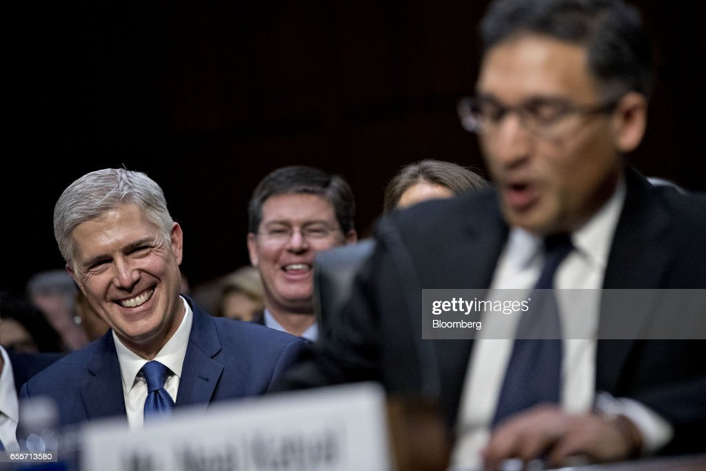 Neil Gorsuch, U.S. Supreme Court nominee for U.S. President Donald Trump, smiles as he is introduced by Neal Katyal, former acting solicitor general, right, during a Senate Judiciary Committee confirmation hearing in Washington, D.C., U.S., on Monday, March 20, 2017. Gorsuch goes before a Senate committee as a heavy favorite, given Republican control, to win confirmation to a lifetime seat on the nations highest court. Photographer: Andrew Harrer/Bloomberg via Getty Images