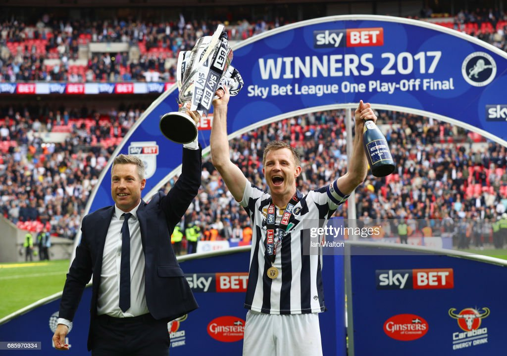 Neil Harris manager of Millwall and captain Tony Craig celebrate victory and promotion with the trophy after the Sky Bet League One Playoff Final between Bradford City and Millwall at Wembley Stadium on May 20, 2017 in London, England.