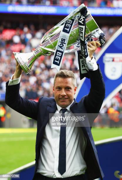 Neil Harris manager of Millwall celebrates victory and promotion with the trophy after the Sky Bet League One Playoff Final between Bradford City and...