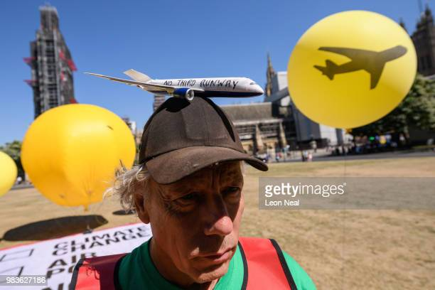 Environmental campaigner Genni Scherer protests against a proposed third runway at Heathrow airport outside the Houses of Parliament on June 25 2018...