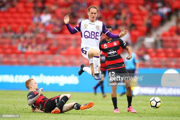 Neil Kilkenny of the Glory jumps over the sliding tackle from Jack Clisby of the Wanderers during the round 23 ALeague match between the Western...