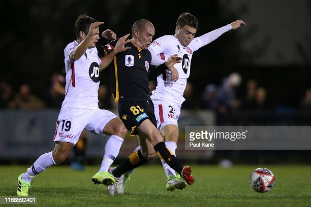 Neil Kilkenny of the Glory passes the ball against Pirmin Schwegler and Nicholas Sullivan of the Wanderers during the FFA Cup Round of 32 match...