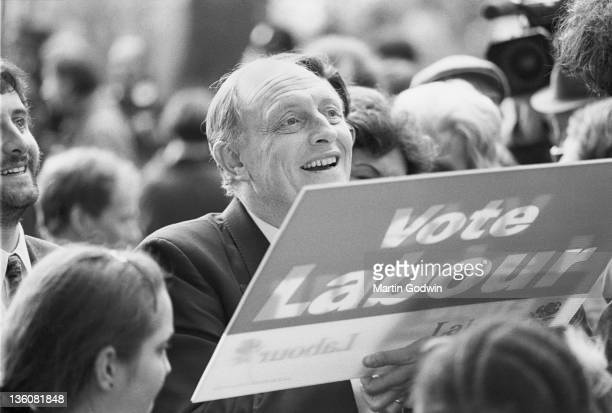 Neil Kinnock campaigning with voters with a 'Vote Labour' placard 2nd April 1992