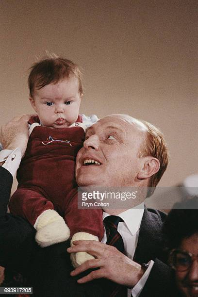 Neil Kinnock UK Labour Party leader poses for a photograph with a young baby as he travelled across the country during the 1987 general election...