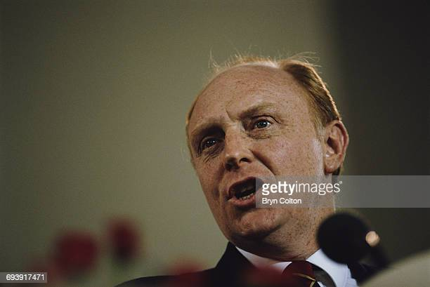 Neil Kinnock UK Labour Party leader speaks to an audience as he stands at a podium covered in red roses during the 1987 general election campaign in...