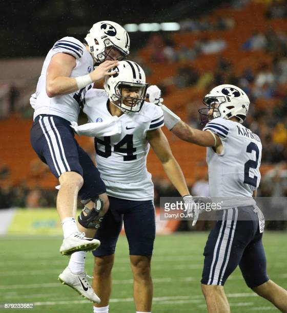 Neil Pau'u of the BYU Cougars is congratulated by teammates Joe Critchlow and Austin Kafentzis after scoring a touchdown during the second half of...