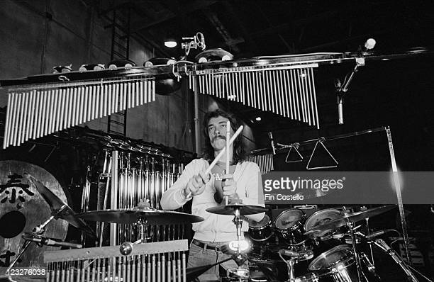 Neil Peart drummer with Canadian rock band Rush behind his drumkit with miniature tubular bells hanging down during a soundcheck ahead of the band's...