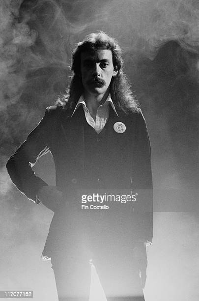 Neil Peart drummer with Canadian rock band Rush poses with one hand on his hip with a smoke behind him in a studio portrait 1978