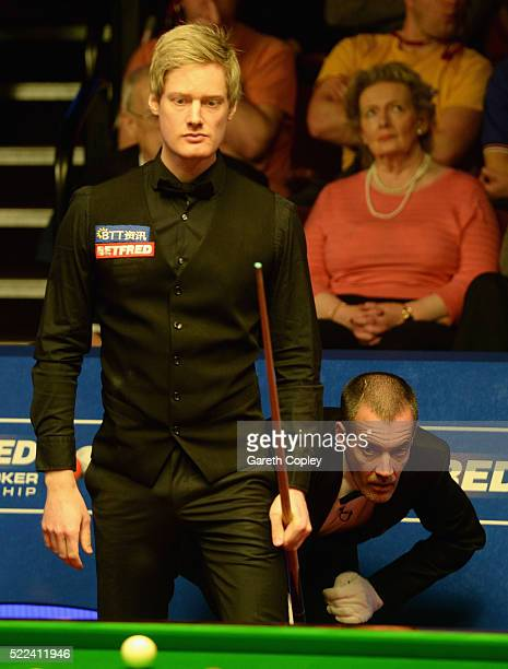 Neil Robertson lines up a shot against Michael Holt alongside referee Olivier Marteel during their first round match of the World Snooker...