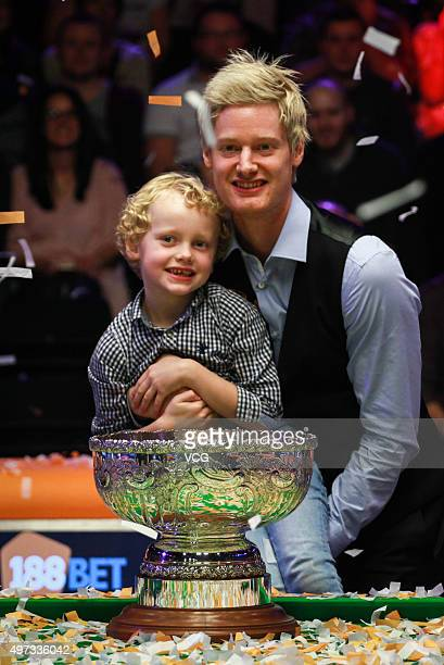 Neil Robertson of Australia celebrates with his son and trophy after final match against Mark Allen of Northern Ireland on day six of Champion of...