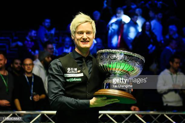 Neil Robertson of Australia celebrates with his trophy after winning the final match against Judd Trump of England during the Champion of Champions...