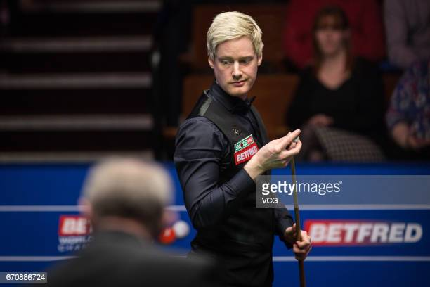 Neil Robertson of Australia chalks the cue during his first round match against Noppon Saengkham of Thailand on day six of Betfred World Championship...