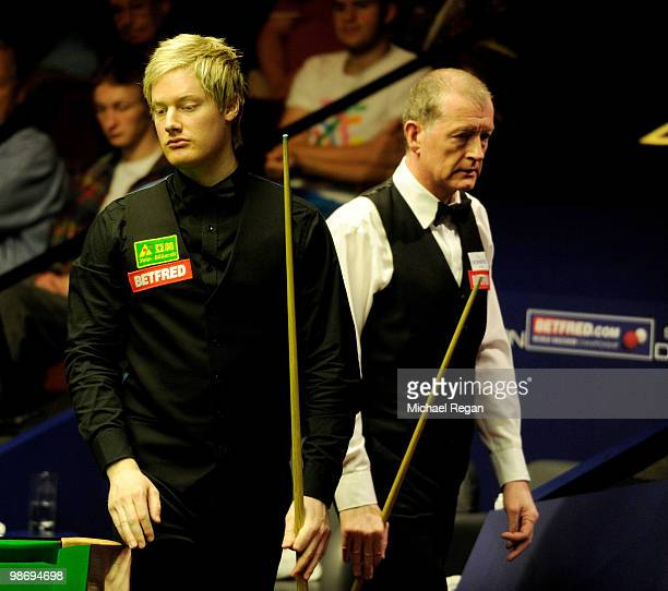 Neil Robertson of Australia eyes up his next shot as Steve Davis of England looks on during the Betfredcom World Snooker Championships at the...