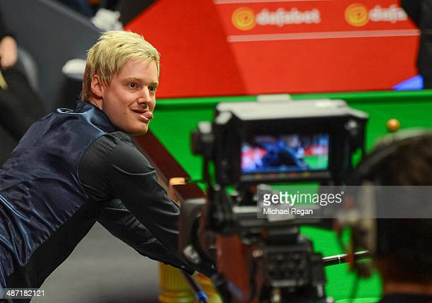 Neil Robertson plays a shot against Mark Allen during their second round match in The Dafabet World Snooker Championship at the Crucible Theatre on...