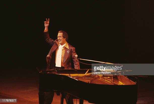 Neil Sedaka US singersongwriter and pianist smiling and waving to the audience as he stands beside his piano during a live concert performance circa...