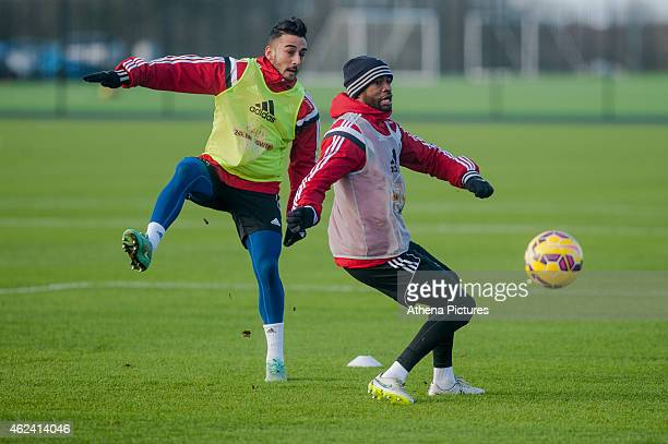 Neil Taylor and Dwight Tiendalli of Swansea City chase the ball during training on January 28 2015 in Swansea Wales