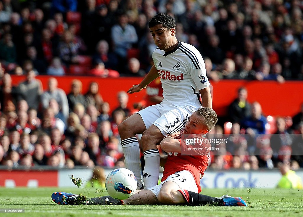 Neil Taylor of Swansea City tangles with Tom Cleverley of Manchester United during the Barclays Premier League match between Manchester United and Swansea City at Old Trafford on 6 May 2012 in Manchester, England.