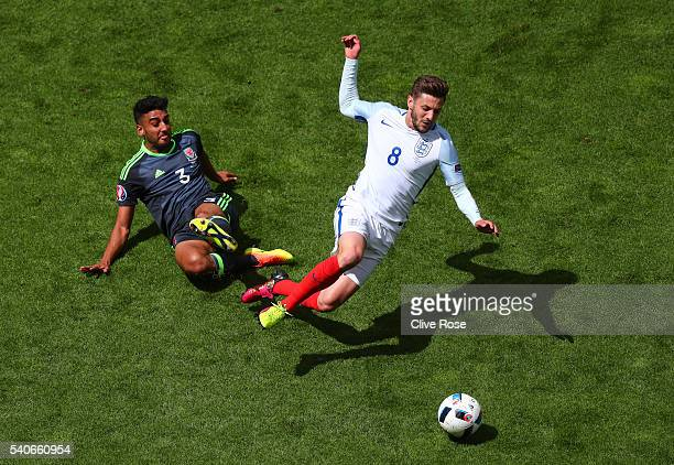 Neil Taylor of Wales tackles Adam Lallana of England during the UEFA EURO 2016 Group B match between England and Wales at Stade Bollaert-Delelis on...