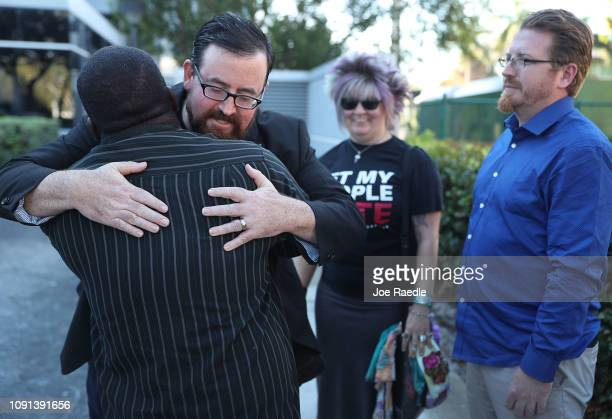 Neil Volz is hugged by Permon Thomas as he and Lance Wissinger arrive to fill out a voter registration form at the Lee Country Supervisor of...