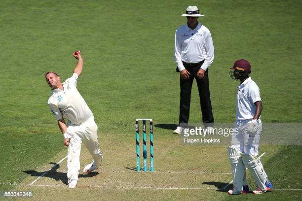 Neil Wagner of New Zealand bowls while umpire Rod Tucker of Australia and Kemar Roach of the West Indies look on during day one of the Test match...
