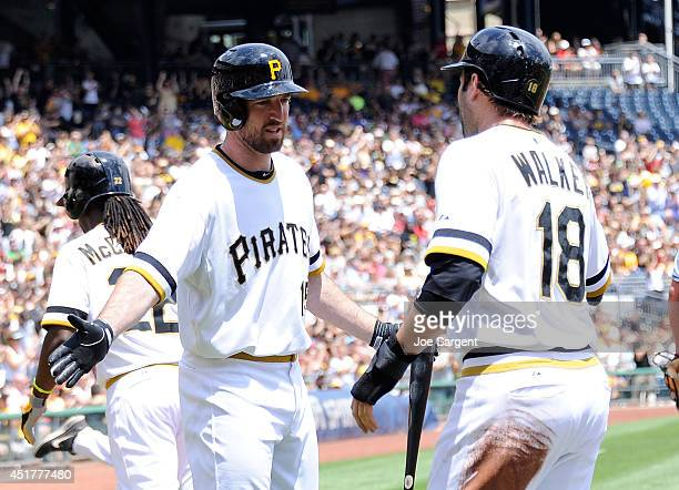 Neil Walker celebrates with Ike Davis of the Pittsburgh Pirates after scoring in the first inning against the Philadelphia Phillies on July 6 2014 at...