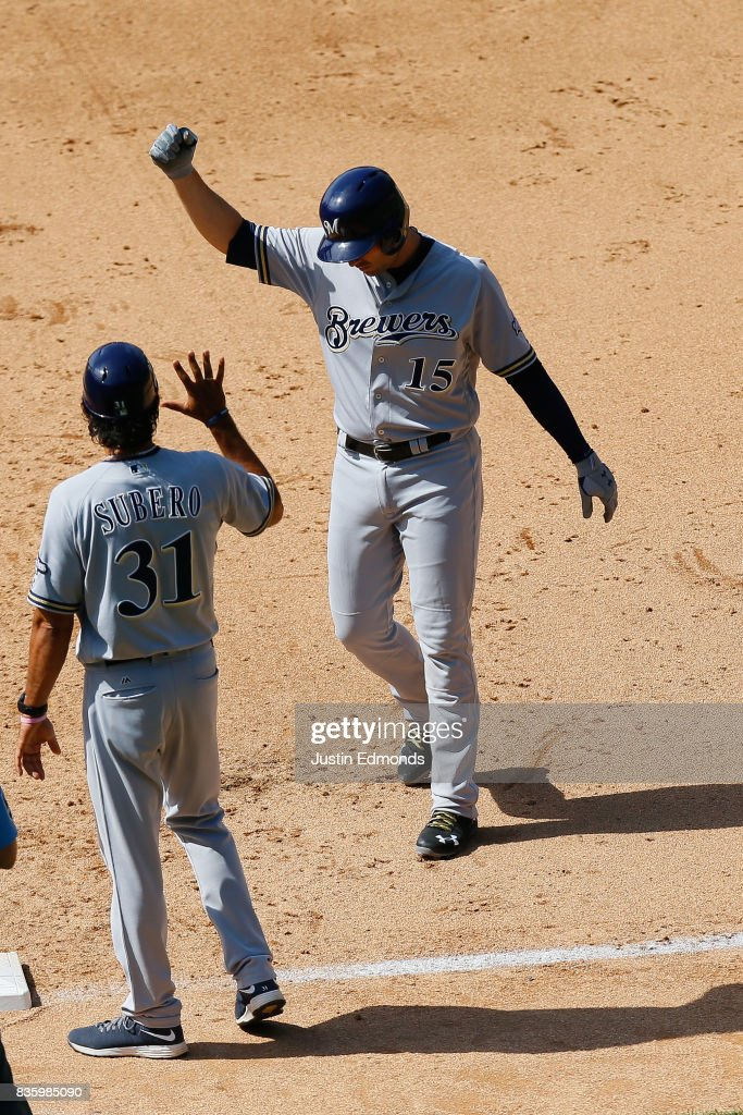 Neil Walker #15 of the Milwaukee Brewers celebrates his pinch hit RBI single with first base coach Carlos Subero during the sixth inning during the game against the Colorado Rockies at Coors Field on August 20, 2017 in Denver, Colorado.