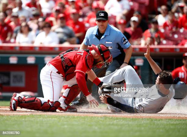 Neil Walker of the Milwaukee Brewers is tagged out at home by Tucker Barnhart of the Cincinnati Reds in the first inning at Great American Ball Park...