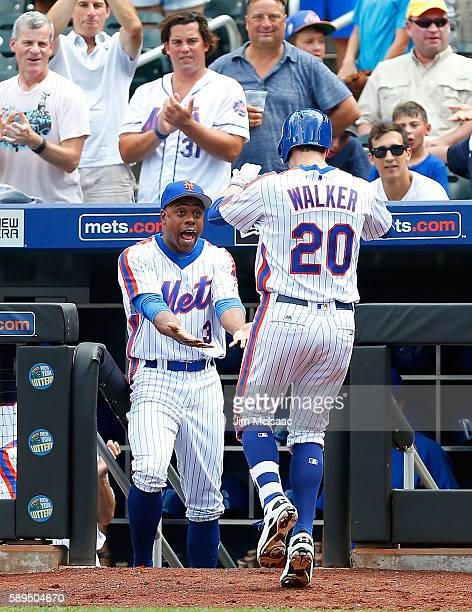 Neil Walker of the New York Mets celebrates his fourth inning home run against the San Diego Padres with teammate Curtis Granderson at Citi Field on...