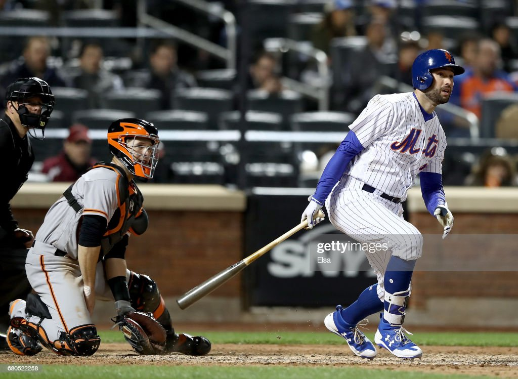 Neil Walker #20 of the New York Mets drives in the game winning run as Buster Posey #28 of the San Francisco Giants defends in the bottom of the ninth inning on May 8, 2017 at Citi Field in the Flushing neighborhood of the Queens borough of New York City.