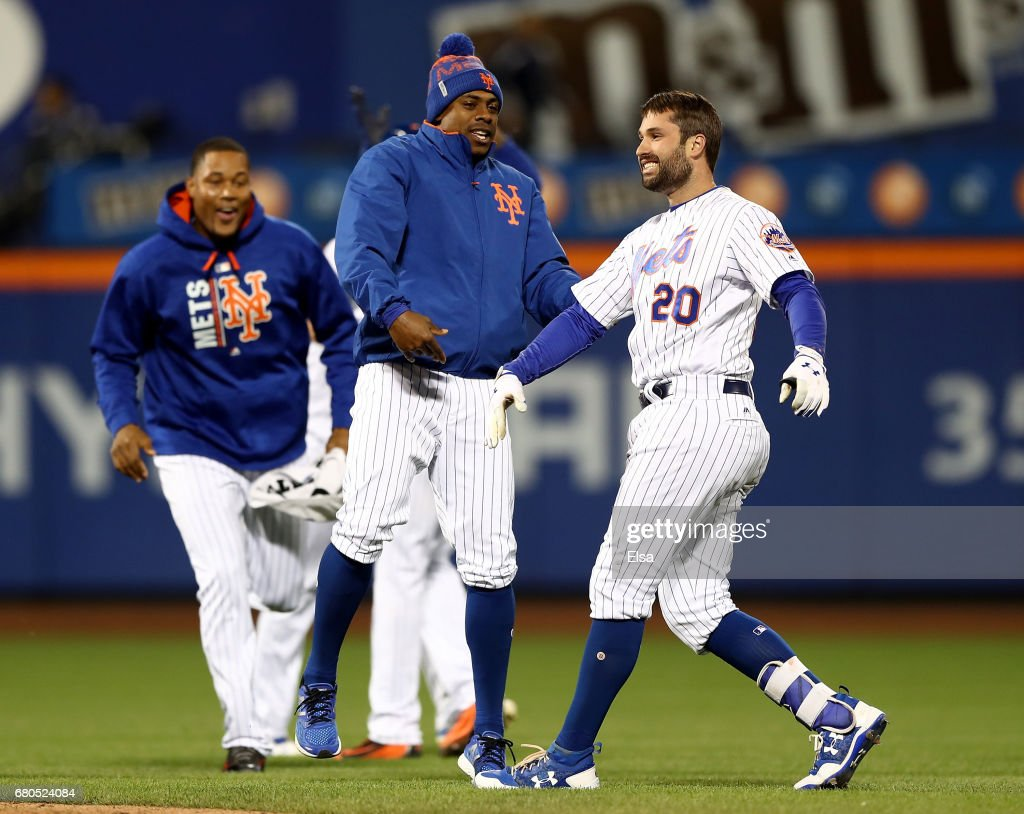 Neil Walker #20 of the New York Mets is congratulated by teammate Curtis Granderson #3 after Walker drove in the game winning run against the San Francisco Giants on May 8, 2017 at Citi Field in the Flushing neighborhood of the Queens borough of New York City.
