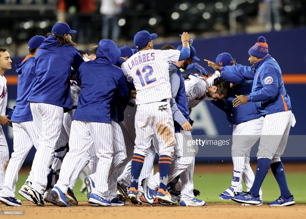 Neil Walker #20 of the New York Mets is surrounded by teammates after he drove in the game winning run against the San Francisco Giants on May 8, 2017 at Citi Field in the Flushing neighborhood of the Queens borough of New York City.