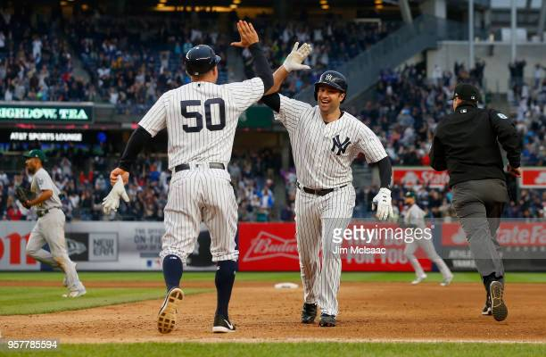 Neil Walker of the New York Yankees celebrates his eleventh inning game winning base hit against the Oakland Athletics with first base coach Reggie...