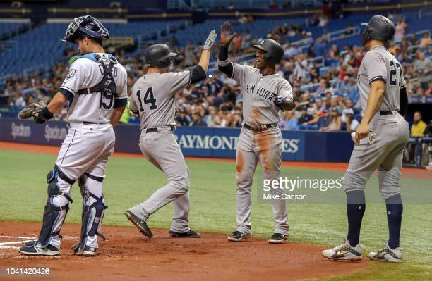 Neil Walker of the New York Yankees is congratulated by Andrew McCutchen and Giancarlo Stanton after hitting all in with a threerun home run as Nick...
