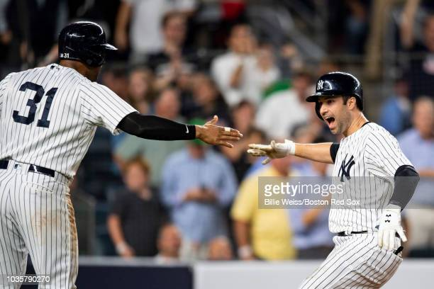 Neil Walker of the New York Yankees reacts with Aaron Hicks after hitting a go ahead three run home run during the seventh inning of a game against...