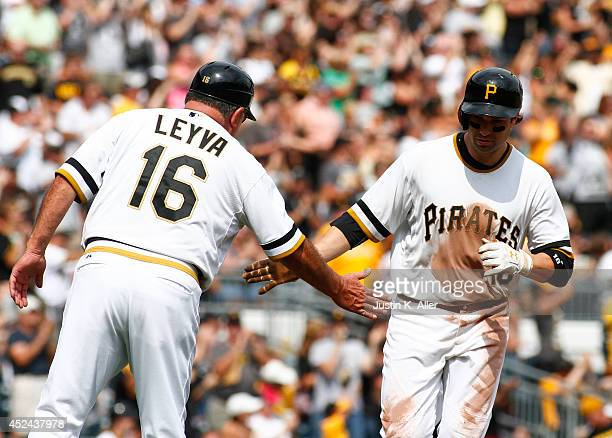 Neil Walker of the Pittsburgh Pirates celebrates with third base coach Nick Leyva after hitting a solo home run in the seventh inning against the...