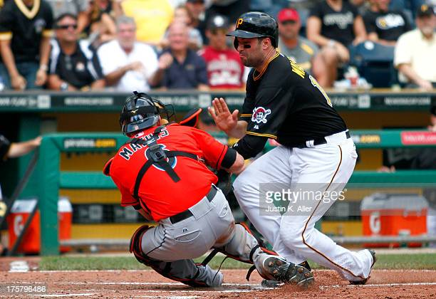 Neil Walker of the Pittsburgh Pirates collides with Jeff Mathis of the Miami Marlins in the fifth inning during the game on August 8 2013 at PNC Park...
