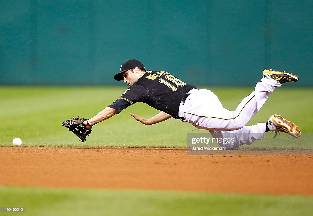 Neil Walker #18 of the Pittsburgh Pirates dives for a ground ball before knocking it down against the St Louis Cardinals during the game at PNC Park on September 28, 2015 in Pittsburgh, Pennsylvania.