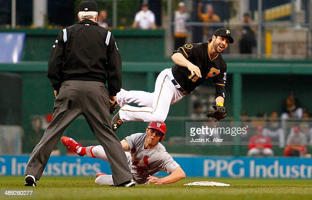 Neil Walker of the Pittsburgh Pirates jumps over Peter Bourjos of the St Louis Cardinals while turning a double play in the second inning during the...