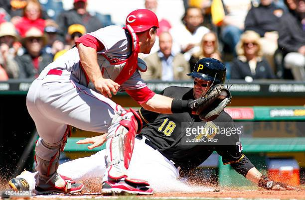 Neil Walker of the Pittsburgh Pirates slides in safe against Devin Mesoraco of the Cincinnati Reds in the first inning during the game at PNC Park...