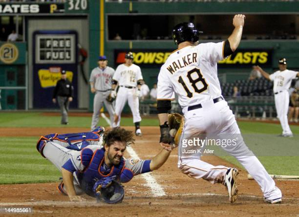 Neil Walker of the Pittsburgh Pirates slides in safe at home to put the Pirates up one run against Mike Nickeas of the New York Mets in the eighth...