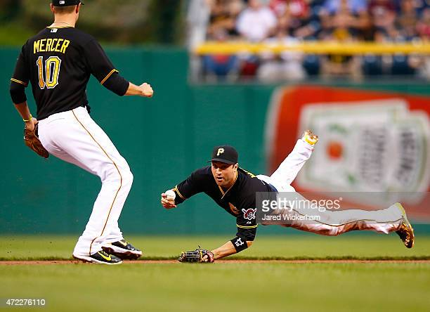 Neil Walker of the Pittsurgh Pirates flips the ball to teammate Jordy Mercer before turning a double play in the second inning against the Cincinnati...