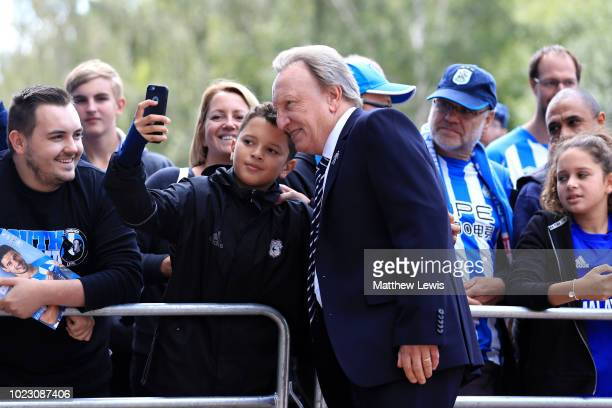 Neil Warnock Manager of Cardiff City poses with a fan on arrival ahead of the Premier League match between Huddersfield Town and Cardiff City at John...
