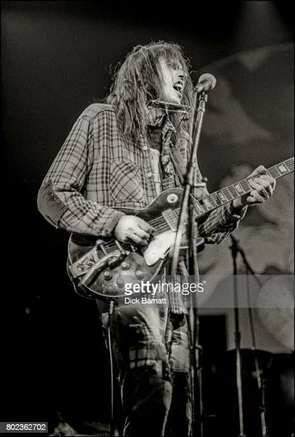 Neil Young and Crazy Horse performing on stage Hammersmith Odeon London March 28th 1976 He is playing a Gibson Les Paul guitar with a Bigsby vibrato...