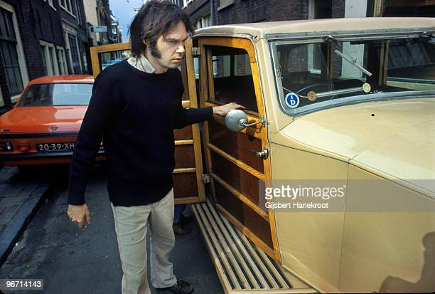 Neil Young checks over The Rolls Royce car he has just purchased in Jordaan Amsterdam Netherlands in 1974
