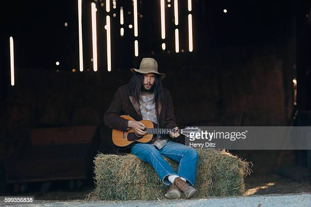Neil Young sits on a bale of hay holding a small acoustic guitar